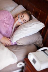 Woman using CPAP BiPap for sleep apnea.